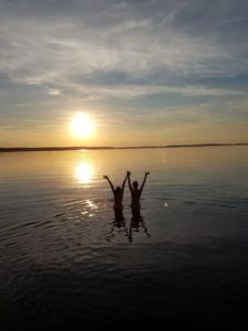 Fröhlicher Mann und Frau mit geöffneten Händen im See
