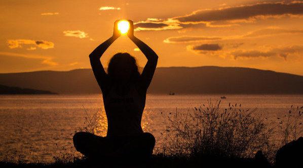 Dame meditiert am Strand